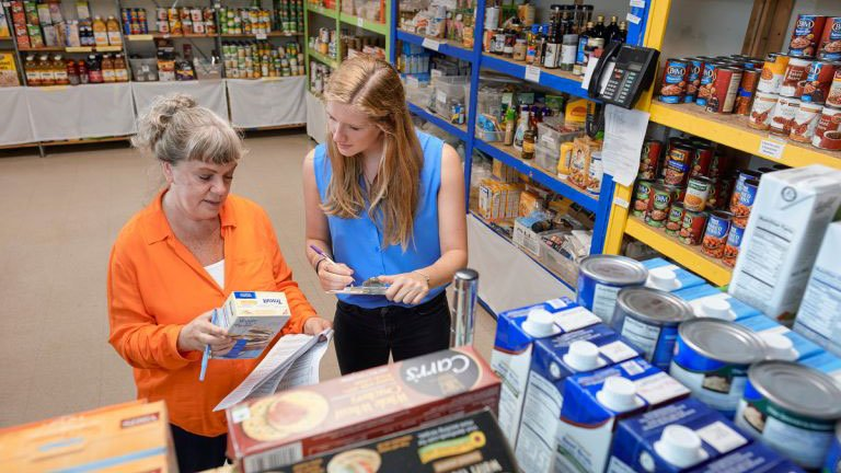 A student works with a HOPE volunteer to organize the food shelf.