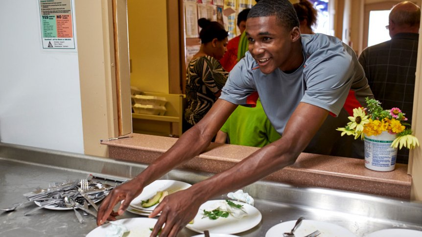 A student helps serve meals at the Congregational Church in Middlebury.