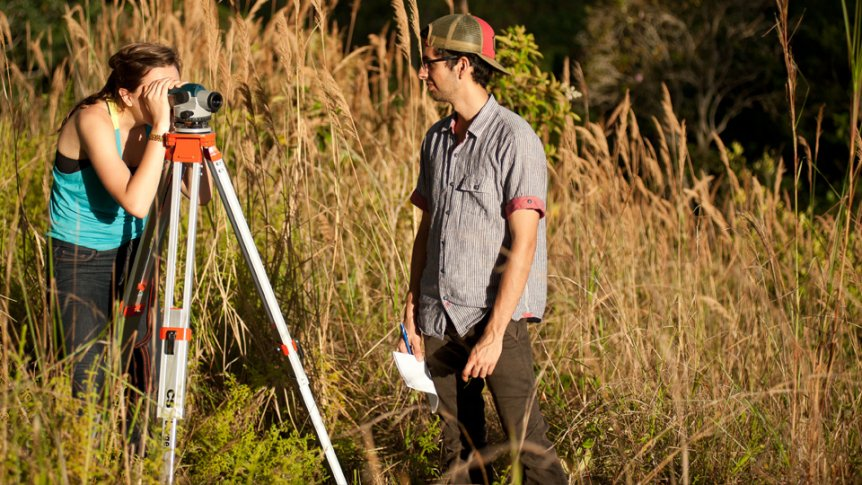 A student in the field looks through a land surveying scope.
