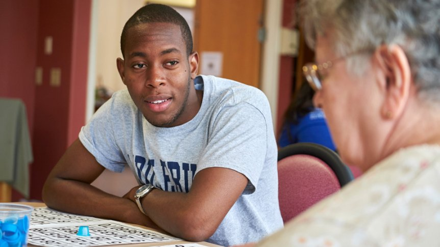 A male student visits a local nursing home to visit with elderly friends.
