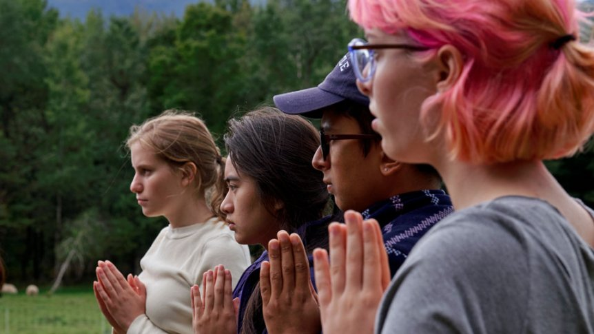 Students meditate together at a serene outdoor spot on campus.