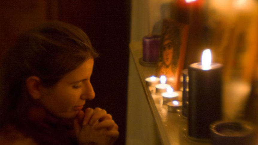 A woman prays by candlelight.
