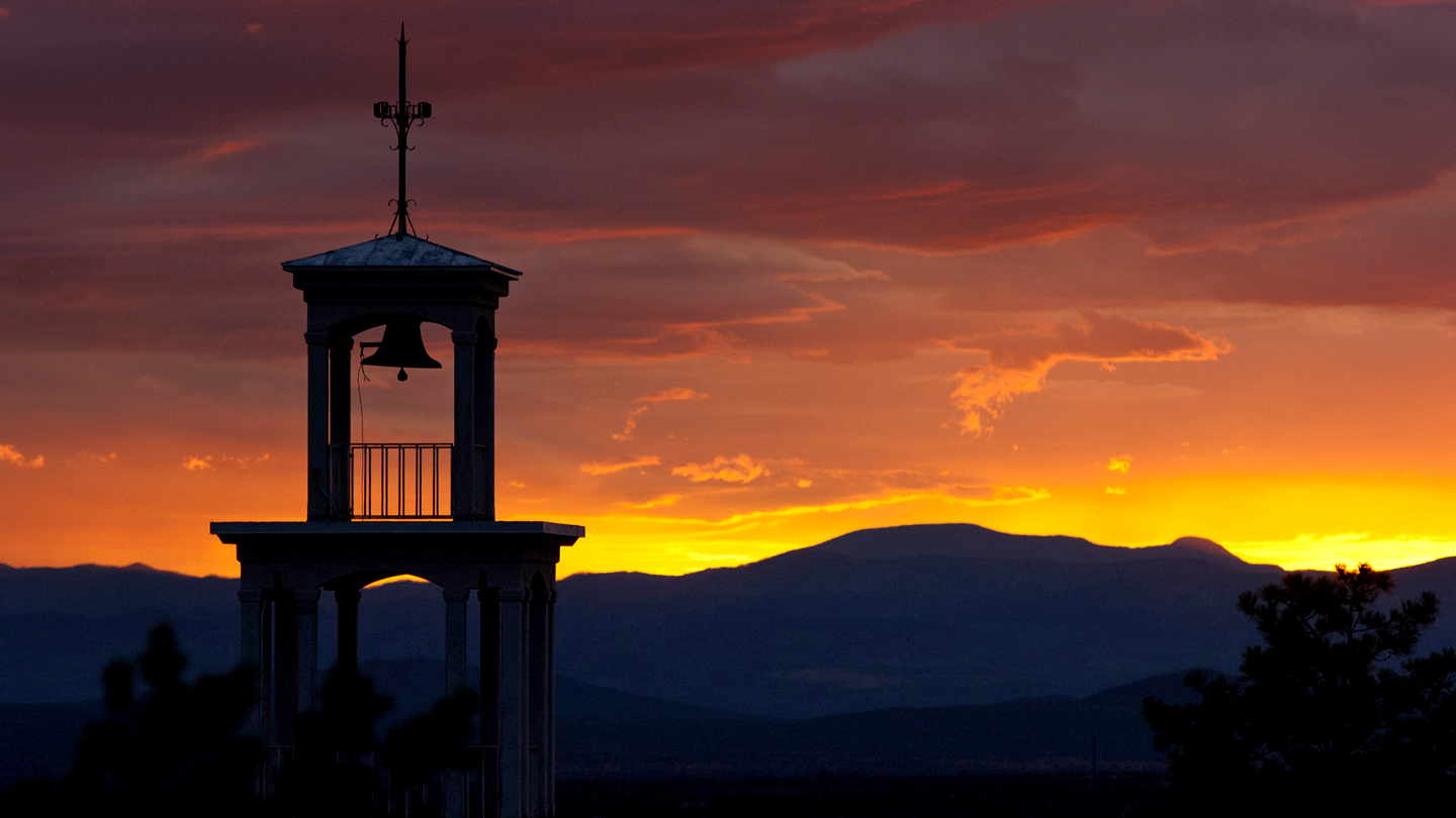 Top of bell tower in Sante Fe with mountains and sunset in background