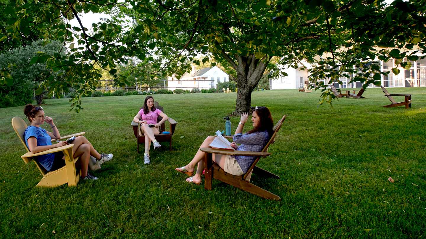 Three female Bread Loaf School of English students sitting outside in adirondack chairs.
