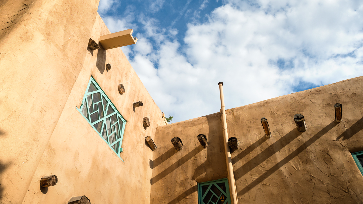 Top of buildings in Santa Fe with blue sky and clouds in background.