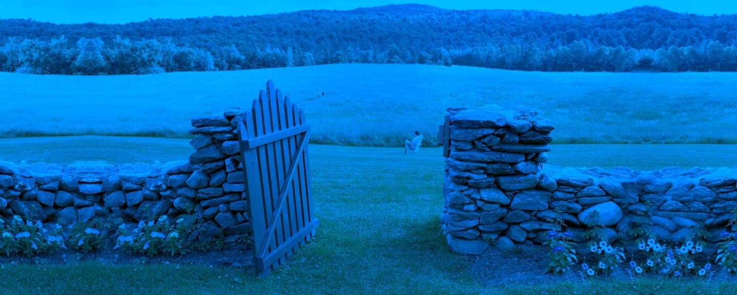 Stone fence with open wooden gate, leading to pasture. Student sitting in chair in distance.