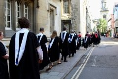 BLSE at Oxford graduates walk down the street in their caps and gowns.