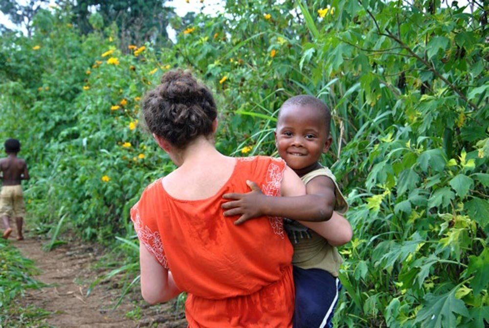 Student carrying her host brother in the fields of Cameroon.