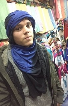 A student in the marketplace with a traditionally wrapped scarf on his head