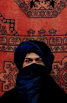 A student with a Berber scarf around his face, in front of a woven rug