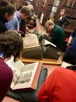 students look at massive old books