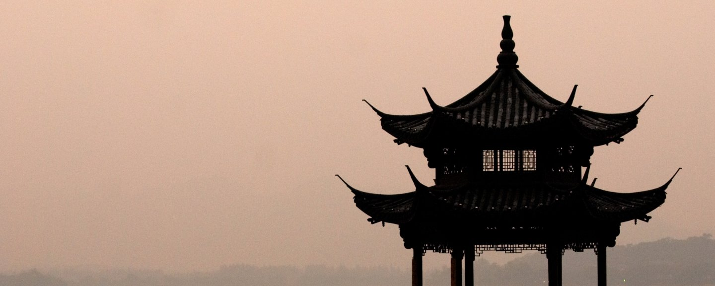 Top of pagoda with hazy, peach-colored sky in background