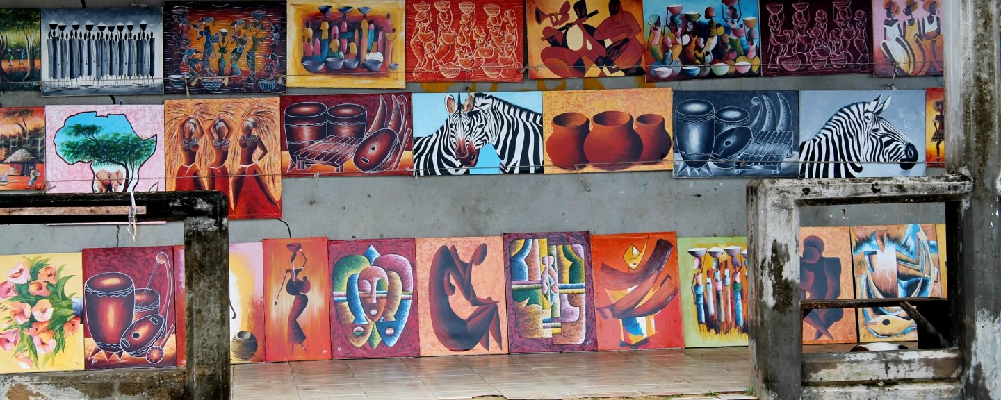 Outdoor market with wall of canvas art for sale