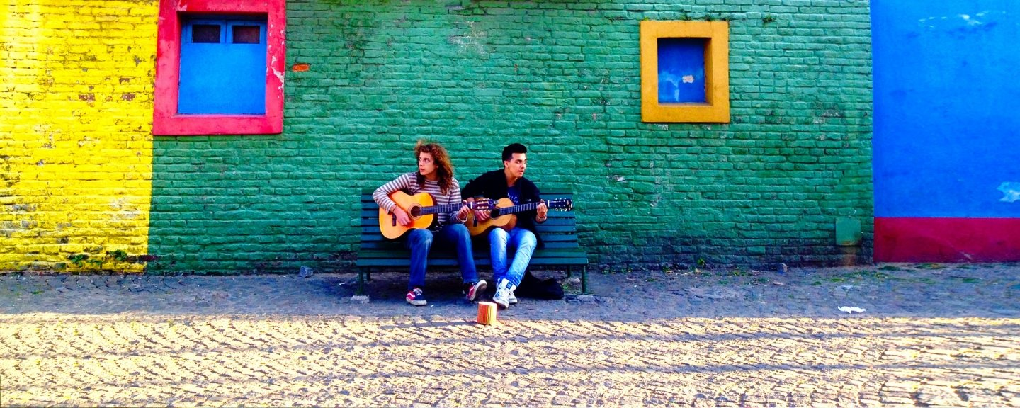 Male and female student sitting in front of colorful wall, playing guitar
