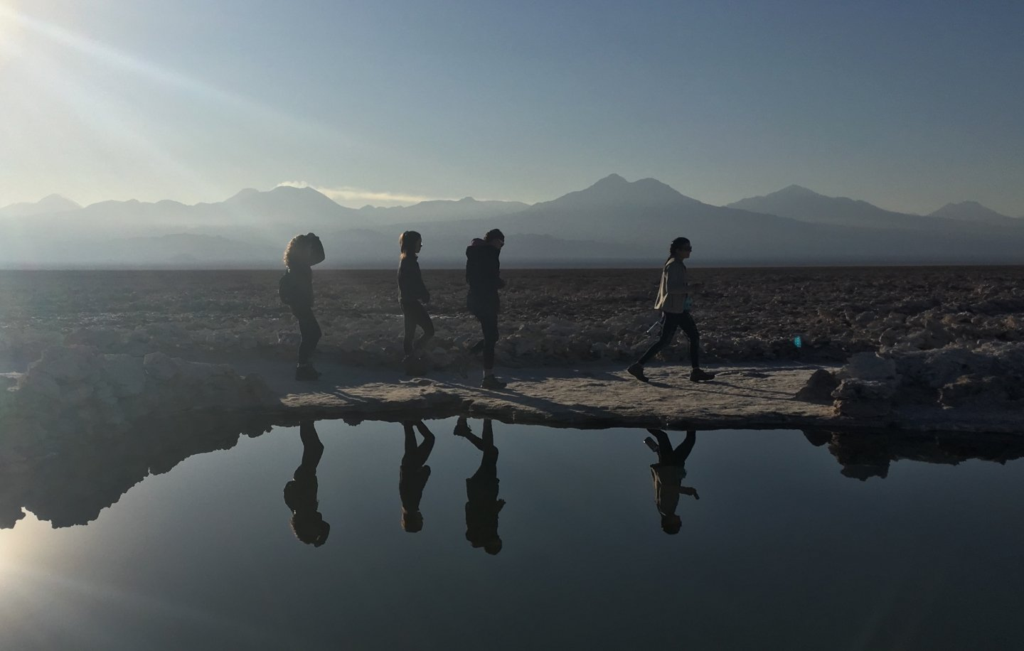 Four students walk in the desert, their reflections in a pool