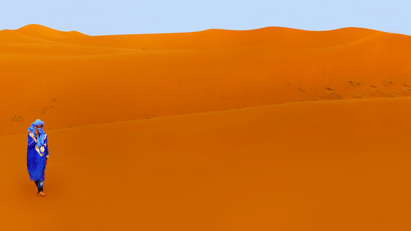 Student walking across desert sand.