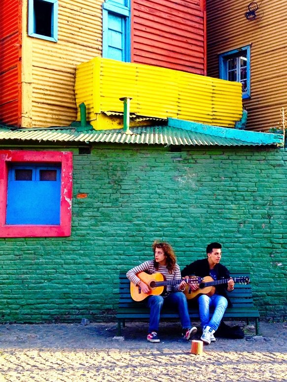 Two students playing music while leaning against a wall in Argentina