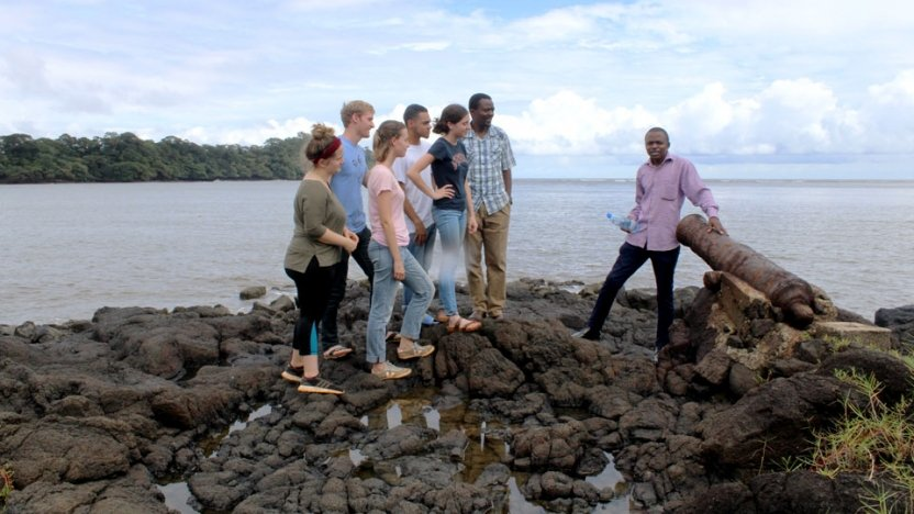 Students sitting and standing on rocks near shore