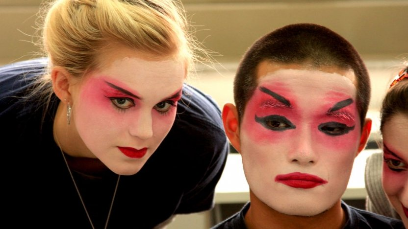 Two students painting their faces in tratidional dance make up