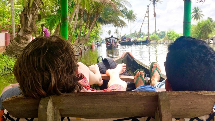 Students sitting in boat on water with feet hanging off side of boat