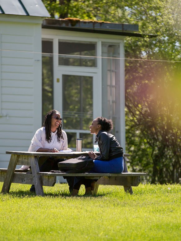 Two students take a break outdoors during the Environmental Writers' Conference.